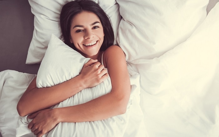 Girl lying on pillows embraces happy one